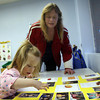 """Gloucester: Deborah Davis watches as her daughter, Nicole Kafka, 3, points out her friends during an open house at the Gloucester Preschool in the Fuller School. """"I hear her sing their names every night,"""" Davis says. Photo by Kate Glass/Gloucester Daily Times"""