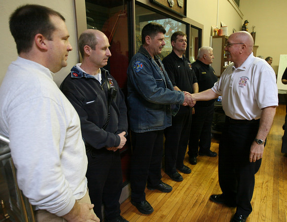 Gloucester: Fire Chief Phil Dench shakes hands with Firefighter Tom Savage after presenting him and Firefighter/Paramedic Jon Sanger, Fire Capt. Bob Fuller, Firefighter/Paramedic Jeff Pool and Police Lt. Joe Aiello with stork pins for their role helping deliver baby Maggie Berthiaume at her family's home on January 23rd. Photo by Kate Glass/Gloucester Daily Times