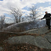 Gloucester: Gloucester Firefighter Doug Sherman hoses down a brush fire on Poles Hill yesterday afternoon. Photo by Kate Glass/Gloucester Daily Times