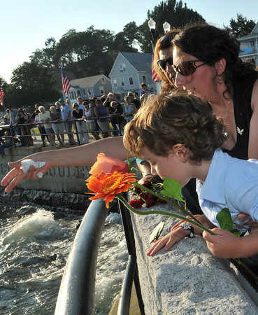 Gloucester: Josie Russo (center) the widow of Matt Russo and her son Saliatore Moses Russo 3, toss flowers into ocean,in memory of her husband Matt Russo and father John Orlando who died at sea when the Patriot went down, at the Fishermen's Memorial held Saturday afternoon.Desi Smith Photo/Gloucester Daily Times.August 15,2009.
