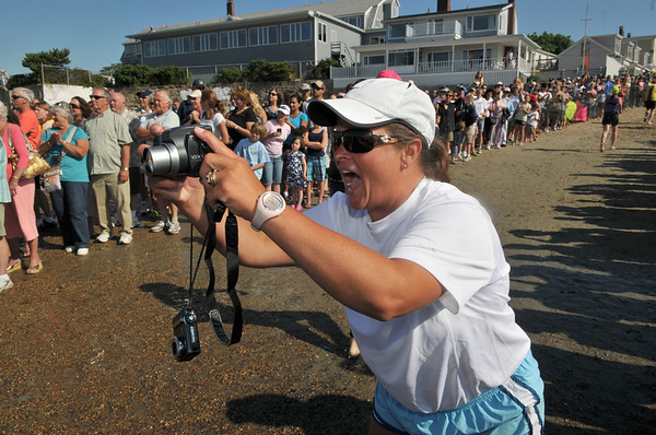 Marcy Plante takes photos and cheers for her friends and colleagues at the Manchester Athletic Club in Manchester as they compete in the 1st Gloucester Triathlon held Sunday morning. Photo by Desi Smith/Gloucester Daily Times