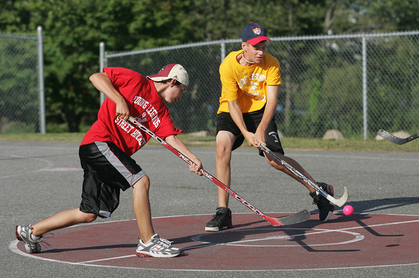 Gloucester: Kyle Edmonds, left, and Jackson Melvin, right, battle for the ball during the last regular season game in the Young Legends Street Hockey League at Stage Fort Park last night. Photo by Kate Glass/Gloucester Daily Times Friday, August 7, 2009