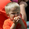 Gloucester: Jackson Periera, 4, takes a big bite of his apple while sitting with his father Peter at the Open Door Summer Lunch Program at Riverdale Park Friday afternoon. This was the last lunch for the summer so along with food, fun games and sundaes made with ice-cream and frozen yogurt kids were also given school supplies for the upcoming school year. Mary Muckenhoupt/Gloucester Daily Times