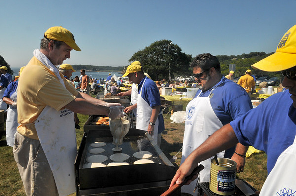 Gloucester: Volunteers Josh Arnold puts pancake batter on the grill, so Rick Doucette can cook the pancakes to be served at the Gloucester Rotary Pancake Breakfast, held at Stage Fort Park Saturday morning. Desi Smith Photo/Gloucester Daily Times. August 15,2009