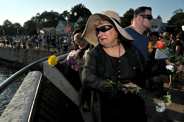 Gloucester:Vincie Curcuru tearfully tosses flowers into the ocean in memory of her brother John Orlando and Matt Russo who lost their lives at sea when the Patriot went down, at the Fishermen's Memorial held Saturday afternoon.Desi Smith Photo/Gloucester Daily Times.August 15,2009.
