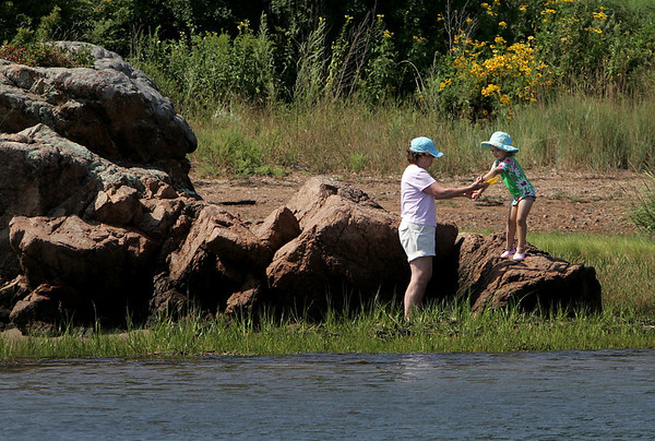 Manchester: Mary Hull of Manchester helps her grandaughter Hannah Powers, 4, down from some rocks while exploring at Tuck's Point Friday afternoon. Mary Muckenhoupt/Gloucester Daily Times