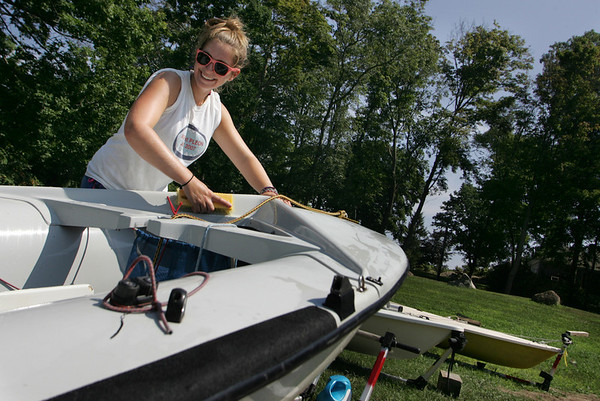 Manchester: Erin Snyder, 17, laughs with her friend Alyssa Fabyan who was helping to clean the other end of the boat as the 420 sailboat race team cleans the boats for the end of their season at Tuck's Point Friday afternoon. Mary Muckenhoupt/Gloucester Daily Times