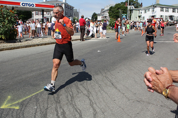 Gloucester's Bob Gillis reacts to the cheering crowd as he starts the second running lap of downtown during the Gloucester Triathlon. Photo by Jeff Pope/Gloucester Daily Times