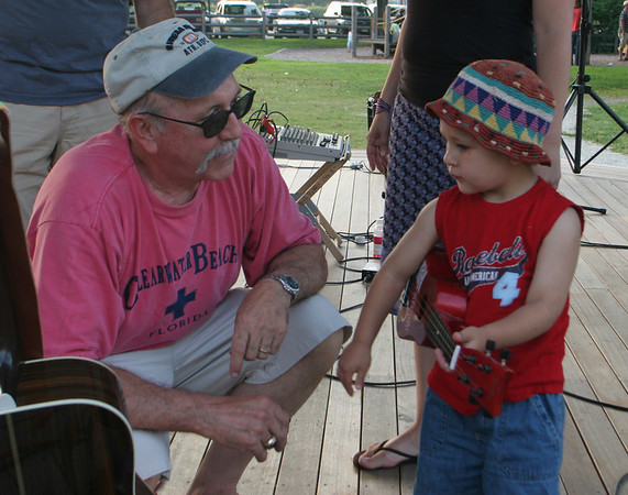 Matias Zapata, 2, shows off his skills to Phil Dench, guitarist and vocalist for the band Mollie's Misfits, during the bands break. Mollie's Misfits are just one of many acts taking part in the Music at Masconomo Park summer concert series in Manchester. Photo by Maria Uminski/ Gloucester Daily Times