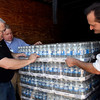 Gloucester: Gloucester Schools Food Services Director Richard Kelleher, left, helps Kevin Bacon, center, and Bob Serra, both of the Eastern Ave Shaws, unload a pallet of water bottles at Gloucester High School yesterday afternoon. Shaws is donating 17,000 bottles of water to Gloucester Schools so they can open despite the water crisis. Kelleher says lunches will be cold sandwiches for the first week and all fruits and vegetables are being delivered pre-prepared to minimize water use. Photo by Kate Glass/Gloucester Daily Times Monday, August 31, 2009
