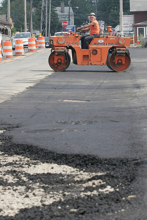 Essex: Fran McHugh drives a steamroller across fresh asphalt along the Causeway in Essex yesterday afternoon in preparation for a temporary widening of the road. Temperatures hovered around 90 degrees, but the crew said work would continue as scheduled. Photo by Kate Glass/Gloucester Daily Times Tuesday, August 18, 2009