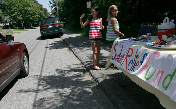 Rockport: Anna Catena, left, and Emma Rukeyser, both 10, wave to customers of their lemonade stand at the intersection of Summer Street and Jerden's Lane, which they set up to raise money for Catena's uncle, Tom Catena, who is a doctor in Sudan. Photo by Kate Glass/Gloucester Daily Times Friday, August 7, 2009