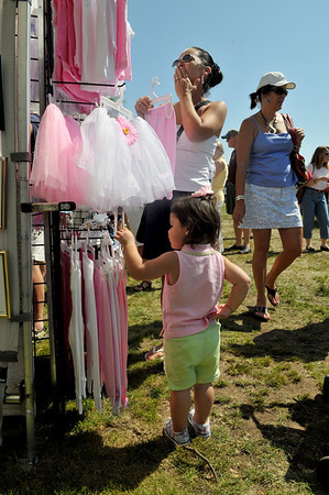 Gloucester: Mackenzie Quartarone 22, month, tries to figure out which outfit will fit her style and taste,as her Grandmother Linda Quartarone looks at other clothing for her Granddaughter while shopping at Glitz Kids of Wakefeild at the Waterfront Festival held at Stage Fort Park Saturday morning. Desi Smith Photo/Gloucester Daily Times. August 15,2009