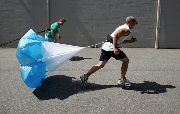Gloucester: David Nicastro, front, runs with a parachute as Larry Flemming runs pulling a sled with weights outside of Aldo's Fitness and Personal  Training Thursday morning. Mary Muckenhoupt/Gloucester Daily Times
