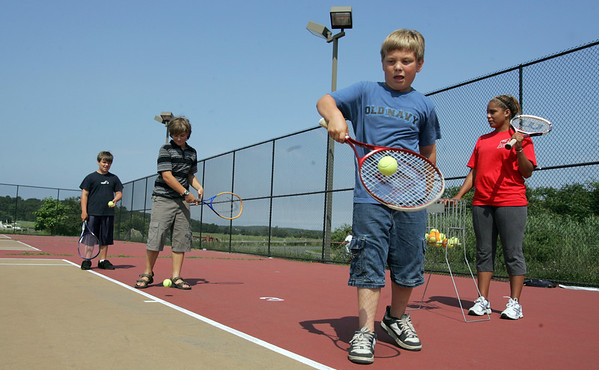 Gloucester: AJ Celentano, 12, left, Danny Wood, 13, center, and Christian Celentano, 9, right, practice their backhands as Maria Evans watches during tennis lessons at Gloucester High School yesterday morning. The lessons are part of The City of Gloucester Summer Rec Program run in partnership with the Cape Ann YMCA. Photo by Kate Glass/Gloucester Daily Times Tuesday, August 11, 2009