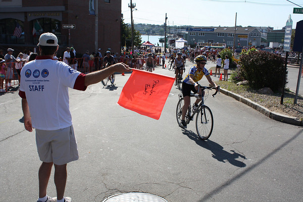 Fitz Lufkin (holding the orange flag) directs racers through Tally's Corner and out Western Avenue at the start of the bicycling leg of the triathlon. Photo by Jeff Pope/Gloucester Daily Times