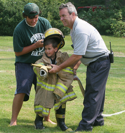 Counselor Steve Driscoll and Lt. Clinton Hatch, of the Manchester Fire Department, give camper A.J. Pallazola, 5, a hand during a relay race after a day of public safety demonstrations at Masconomo Park in Manchester for the Manchester Summer Playground program. Photo by Maria Uminski/ Gloucester Daily Times