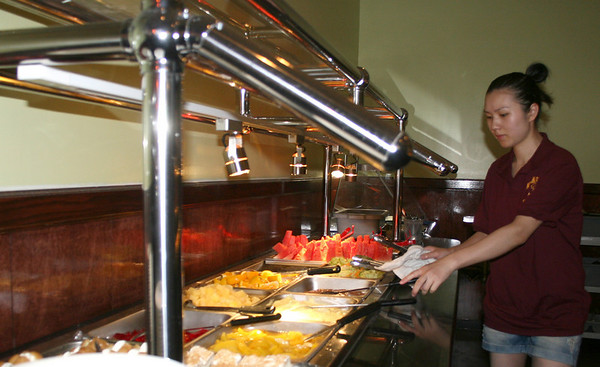 Gloucester: June Wu, one of the owners of No.1. China Buffet, prepares a lunch buffet on Monday morning. Yama Wok reopened as No.1. China Buffet on August 5th, expanded their space for sitdown dining and they offer variety of meals. <br /> Silvie Lockerova/Gloucester Daily Times