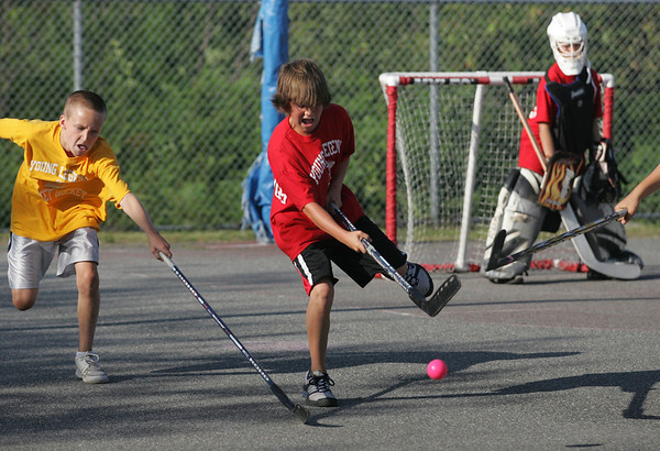 Gloucester: Joe Ogonowsky, left, and Terrance Lane, center, battle for the ball as goalie Brady Parisi looks on during the last regular season game in the Young Legends Street Hockey League at Stage Fort Park last night. Photo by Kate Glass/Gloucester Daily Times Friday, August 7, 2009