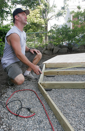 Gloucester: Andy Hillstrand of The Deadliest Catch measures a gazebo that is being installed in the backyard of Gloucester resident Jamie Marshall for the show Indoors Out. Photo by Kate Glass/Gloucester Daily Times Tuesday, August 4, 2009