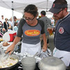Melissa Hart and her brother Christopher Sallah worked together to pull off a win for Sugar Magnolias yesterday during the Seafood Throwdown at the Cape Ann Farmers' Market against the Alchemy Cafe. One of the secret ingredients that both teams had to use was Cod which Melissa poached in a butter with tarragon and garlic. Photo by Maria Uminski/ Gloucester Daily Times