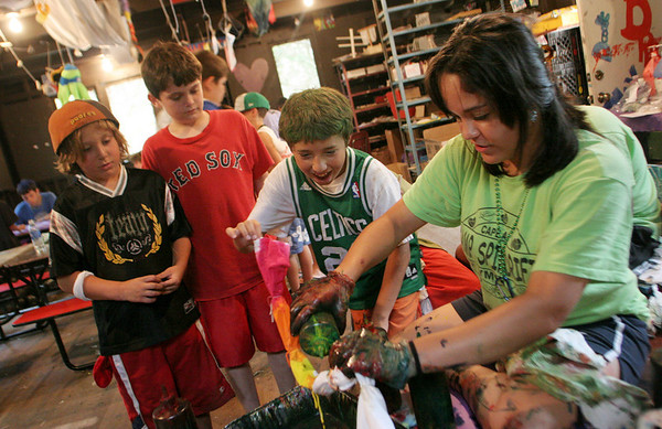 Gloucester: Joey Marcantonio, 12, watches as camp counselor Ellie Cornavaca tie-dyes his t-shirt while his friends, Collin MacDonald and Max Nicastro, left, at Camp Spindrift Thursday afternoon. Mary Muckenhoupt/Gloucester Daily Times