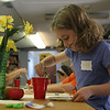 Kyla, 8, of Rockport cleans her brush before continuing to paint her picture she drew of the vase of yellow flowers at the Rockport Art Association during a Drawing and Painting Session with Becky Merry. Photo by Maria Uminski/ Gloucester Daily Times