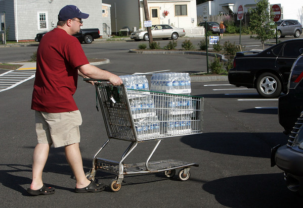 Gloucester: Dennis Acker leaves Shaws on Railroad Avenue with six 24 packs of water after the city declared the drinking water unsafe Friday afternoon. Mary Muckenhoupt/Gloucester Daily Times
