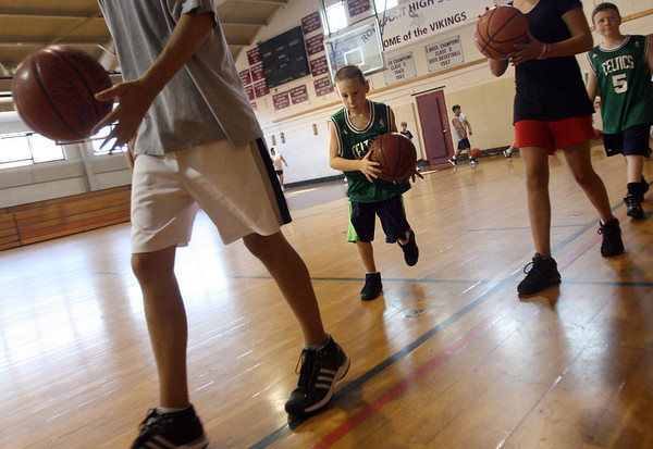 Rockport: William Altman dribbles between kids at the Rockport High School gym during the Rockport Basketball Clinic yesterday morning. Former NBA player Walter Palmer, boys varsity coach Tim St. Laurent, and members of the boys varsity team teach fundamental skills of the game. Photo by Kate Glass/Gloucester Daily Times Tuesday, August 18, 2009