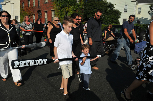 Gloucester: Josie Russo (center in black) the widow of Matt Russo and her nephew Saliatore Eric Russo 12, (left) and josie's son Saliatore Moses Russo 3, carry a oar in memory of the Patriot and its crew, at the Fishermen's Memorial held Saturday afternoon.Desi Smith Photo/Gloucester Daily Times.August 15,2009.