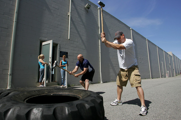 Gloucester: Tom Scola, right, and Kevin Doble hit giant tires with sledge hammers at Aldo's Fitness and Personal Training Thursday morning. Mary Muckenhoupt/Gloucester Daily Times