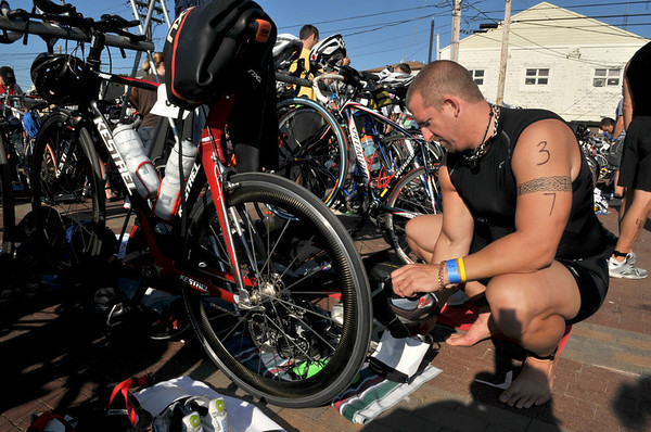 Jamie Ranney of Nantucket gets his bike gear together at St Peter's Square so he can quickly mount his bike after his swim to save time during Gloucester's 1st Triathlon. Photo by Desi Smith/Gloucester Daily Times