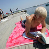 "Essex: Michael Webber reads a book on the dock at Conomo Point Saturday morning.  Webber was pretty relaxed in the sun with his book, ""The Long Run"" but was bothered by pestering greenhead flies. Mary Muckenhupt.Gloucester Daily times"