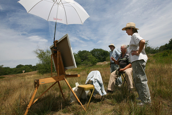 Gloucester: David Curtis, center, discusses color with Tom Amend and Elizabeth Bish during a painting workshop at Seine Field yesterday afternoon. Tom and Elizabeth met at a painting workshop in France and frequently take lessons with Curtis. Photo by Kate Glass/Gloucester Daily Times