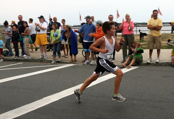 Charles Davis, 12, of Manchester gets a loud applause from the crowd as he approaches the finish line of Run Gloucester! a 7-mile road race, yesterday morning. Photo by Kate Glass/Gloucester Daily Times