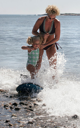 Rockport: Kristen Pino holds her daughter, Isabella Rapp, 3, as she tries to stay on a boogie board through a wave at Pebble Beach on Monday. Photo by Kate Glass/Gloucester Daily Times