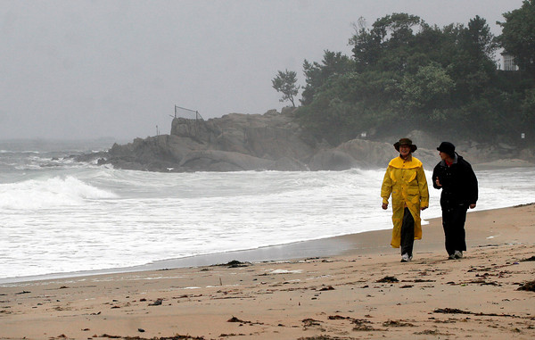 """Manchester: Sheila Hill of Manchester and Sue Lotz of Groton walk along Singing Beach yesterday afternoon. """"We've had such a wonderful summer, but this day is a treasure too,"""" Hill says of the high surf and rain. Photo by Kate Glass/Gloucester Daily Times"""