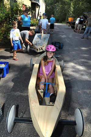 Gloucester: Sara Wheeler 9, waits in line for her inspection in a Seine Boat designed and built by her father David behind her working on another fishbox car AKA The Shark that still needs paint, Sunday morning at C.B Fisk Industrial Park. All cars and drivers have to be registerd,weighed and inspected on that date.  Desi Smith/Gloucester Daily Times. August 29,2010.