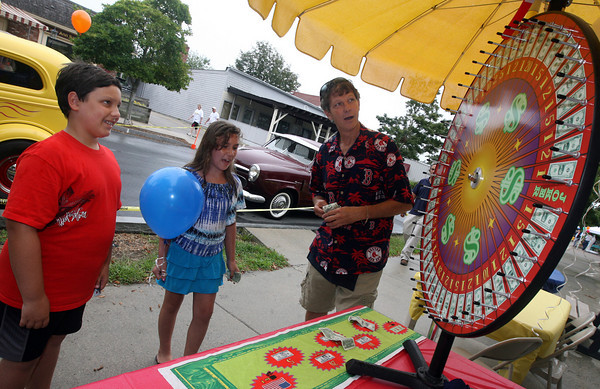 "Gloucester: Kevin Nolan and his sister, Ericca Nolan try their luck at the ""casino"" run by Doug Shatford during Magnolia's Giant Sidewalk Bazaar and Roadshow on Sunday. The event was a benefit for the Magnolia Historical Society. Photo by Kate Glass/Gloucester Daily Times"