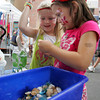 Gloucester: Anna Philips, 4, and Isabelle Nixon, 6, make still life aquariums in a water bottle at the Eastern Point Day School table during Sidewalk Days held on Main Street Thursday afternoon. The aquariums didn't have any fish but had seashells, sea glass, and plenty of sparkley jewels and glitter. Mary Muckenhoupt/Gloucester Daily Times