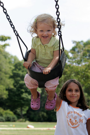 Manchester: Addie Woodruff, 21 months, gets a push from Ali Karafotias, 7, at Masconomo Park Thursday morning. Addie was smiling at her brother Jack, 3, who was stading in front of her making a silly face. Mary Muckenhoupt/Gloucester Daily Times