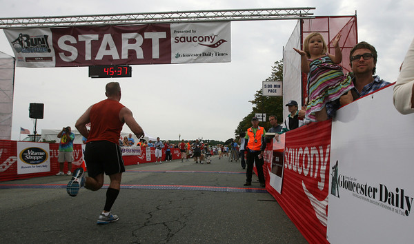 Gloucester: Damien Johnson holds his daughter, Juliet, as they cheer on the runners finishing Run Gloucester! yesterday morning. Photo by Kate Glass/Gloucester Daily Times