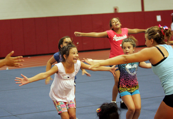 Gloucester: Lillie Favazza, 8, smiles at Abby Papp, 15, a Gloucester High School cheerleader while learning a routine at the Gloucester Cheeleaders' Mini Camp at Gloucester Field House Wednesday afternoon.  The cheerleading camp was held Tuesday through Thursday for children ages 5 to 13 with cheers taught by Gloucester High School cheerleaders. Mary Muckenhoupt/Gloucester Daily Times