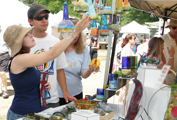 Gloucester: Andria Rogers checks out some glass wind chimes with Victor Quesada of Gloucester at the Waterfront Festival Saturday afternoon at Stage Fort Park. Mary Muckenhoupt/Gloucester Daily Times