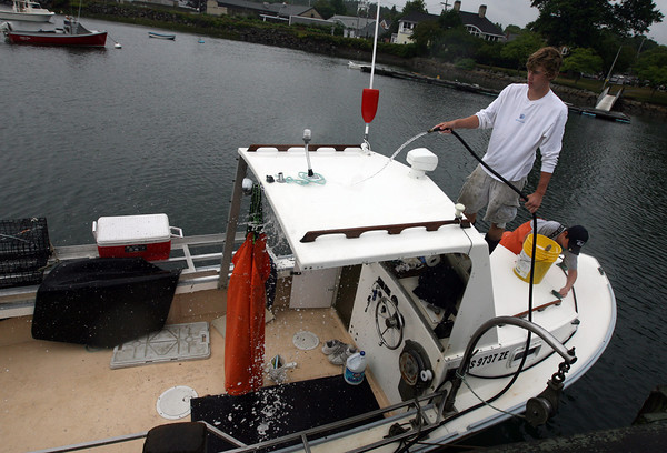 Manchester: Cam Smith, 17, hoses down his lobster boat, Brittannika, as his cousin, Henry Doucette, 13, scrubs the bow on Monday afternoon. The two go lobstering during their summer vacation and were taking advantage of the rainy weather to get some maintenance work done. Photo by Kate Glass/Gloucester Daily Times