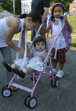 Gloucester: Kali Judd, a fourth grade student at Veterans Memorial School, reaches to pick up her youngest sister, Kara, 1, as her other sister, Kaylin, who started kindergarten yesterday, holds the stroller. Photo by Kate Glass/Gloucester Daily Times