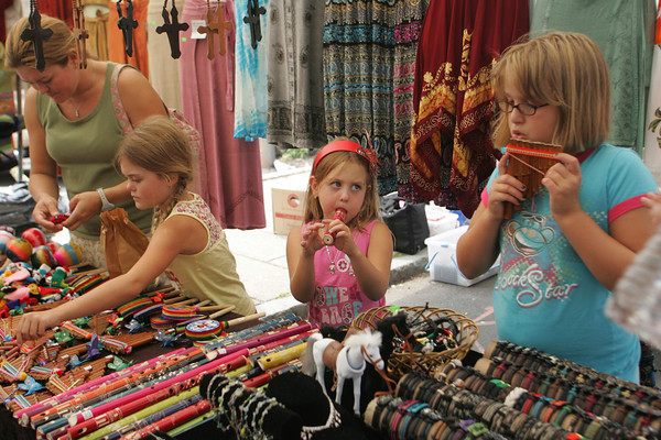 Gloucester: Solenn Minogue, 7, looks up at Molly Martin, 8, right, as the two try out musical instruments at one of the tents during Sidewalk Days held on Main Street Thursday afternoon. Also pictured is Minoque's sister Nola, 7, and mother Delphine, left.  Mary Muckenhoupt/Gloucester Daily Times
