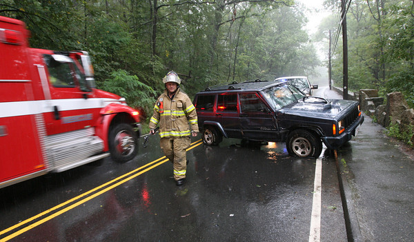 Gloucester: Gloucester Firefighter Mike Smith surveys the scene of an accident on Washington Street near the stone bridge yesterday morning. The driver hydroplaned and hit a telephone pole. No injuries were reported. Photo by Kate Glass/Gloucester Daily Times