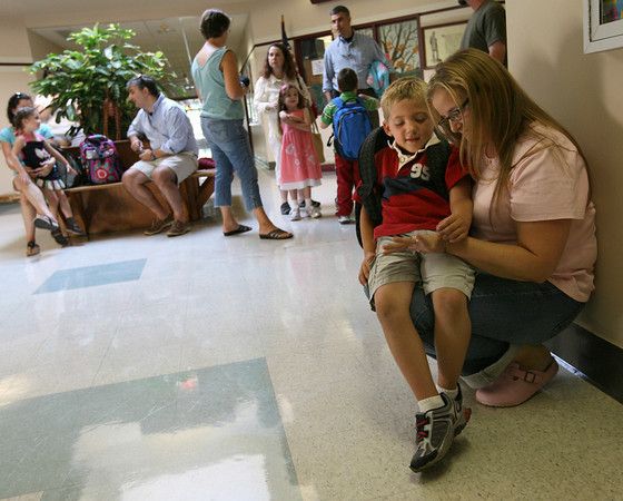Gloucester: Benjamin Graham looks at the rings of his mother, Katie Graham, as they wait to check out his kindergarten class during the first day of school at Rockport Elementary School yesterday. Photo by Kate Glass/Gloucester Daily Times
