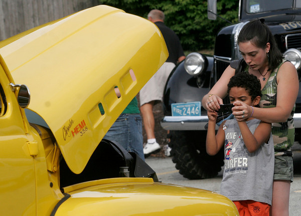 Rockport: Starsha Tupper of Rockport helps her cousin, David Avila, take photos of the different vehicles on display at Den-Mar Rehab and Nursing Center's Antique Car Show on Tuesday. Photo by Kate Glass/Gloucester Daily Times